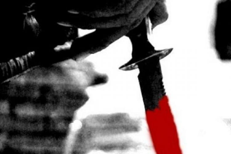 A black and white picture where only half a knife is red held by a persons hand