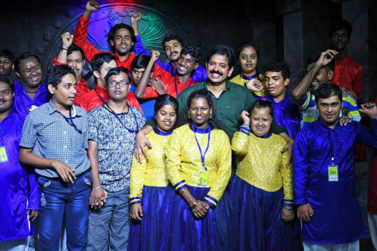 Muthukad surrounded by children with disability wearing marching clothes - yellow and blue and red -- after a magic performance