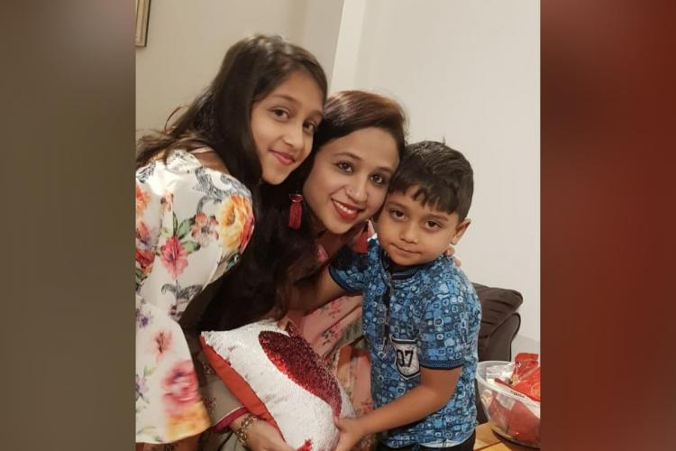 Seema Banu Syed is hugging her two children She is wearing a green saree and red earrings