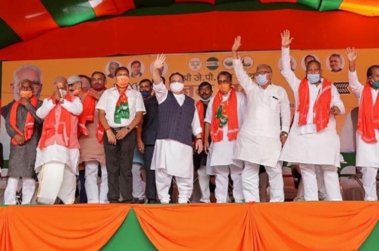 NDA leaders standing and waving on stage in Bihar