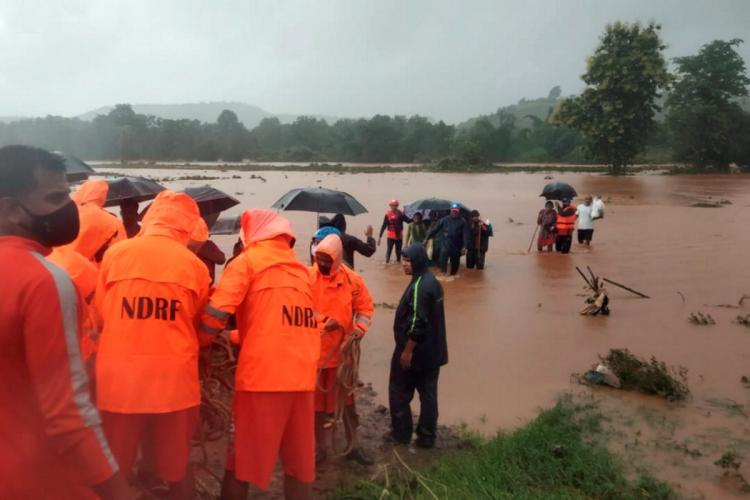 NDRF officials in fluorescent orange jackets standing next to a flooded river