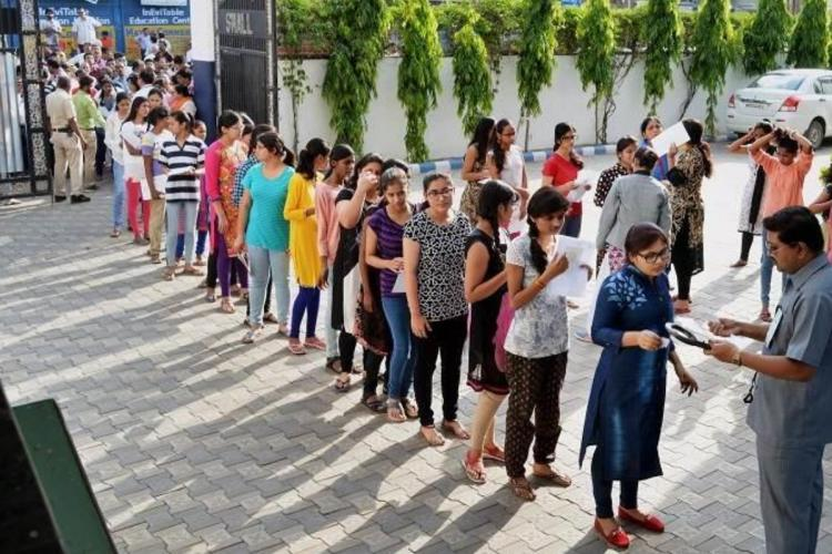 The students standing in a line to enter the exam hall for attending NEET examinations