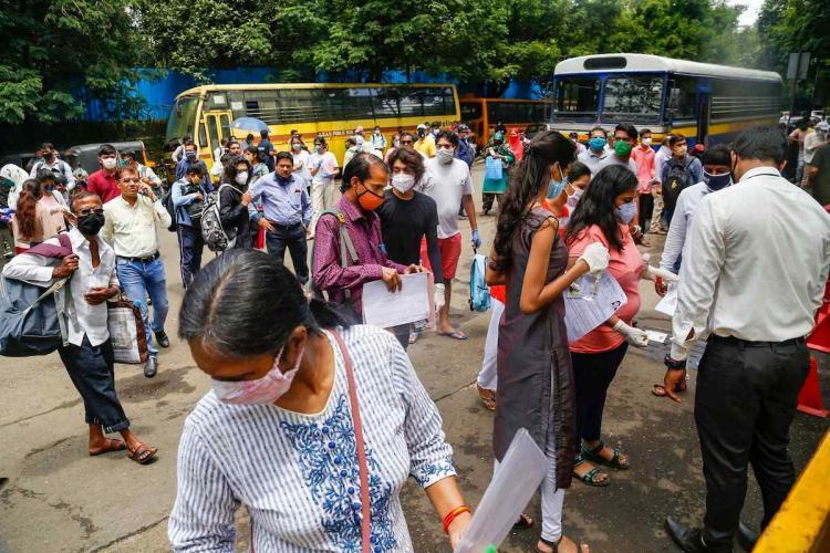 NEET aspirants standing in front of exam centres to undergo mandatory temperature screening