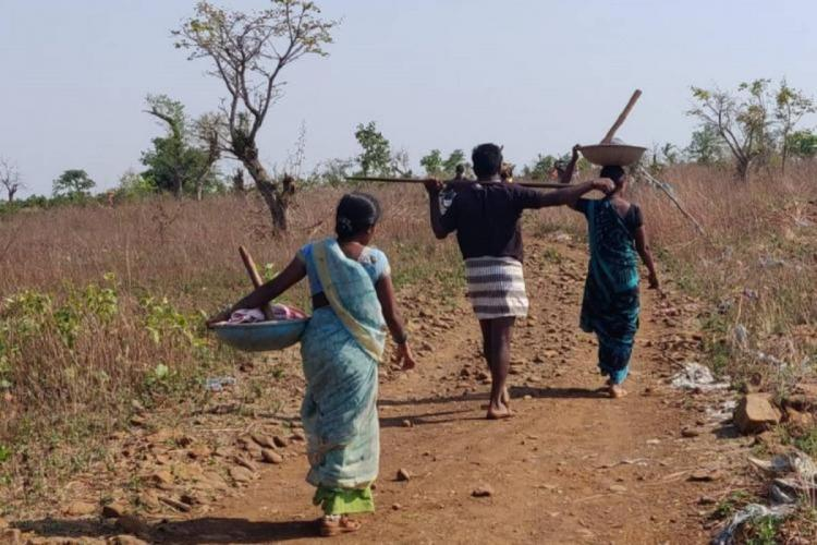 Two women and a man walking with construction equipment among fields in a village