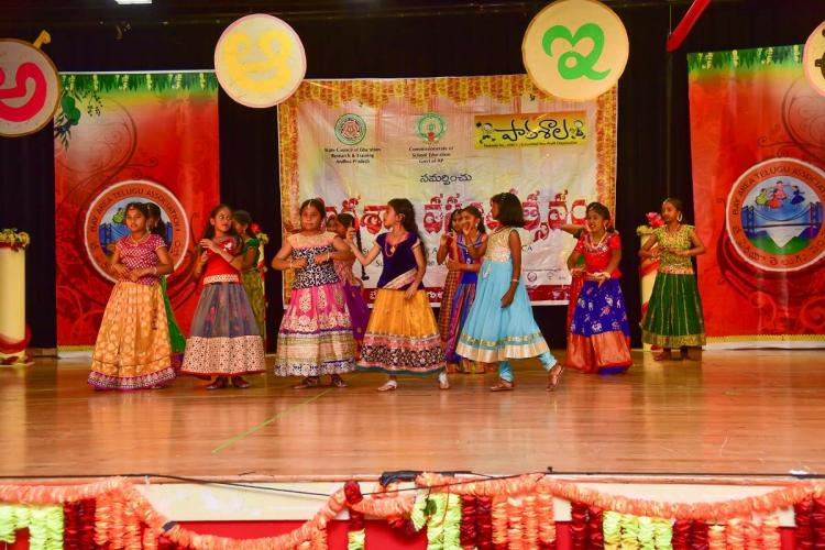 Children wearing traditional costumes are seem dancing on the floor where in telugu alphabet were decorated