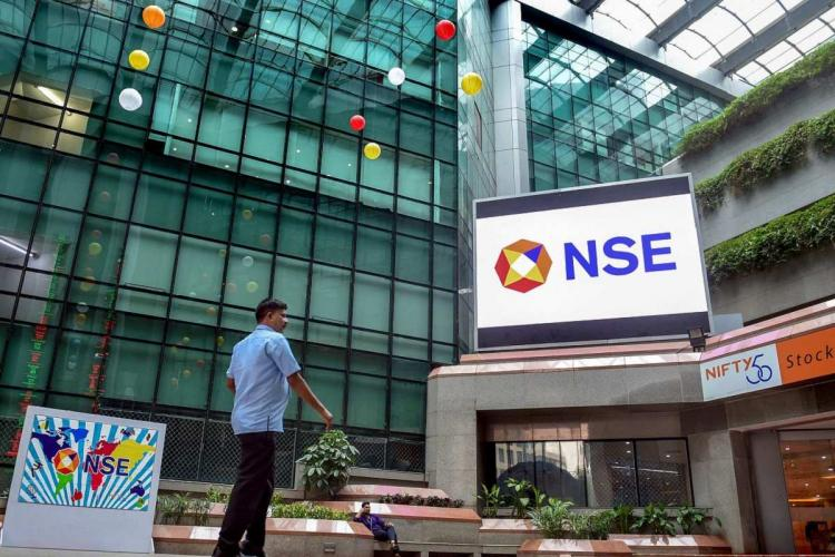 Man standing in front of the NSE headquarters with logo displayed
