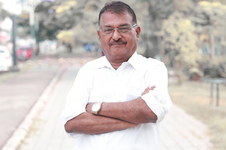 N Venugopal standing on a footpath near a deserted road He is wearing a white shirt and is looking at the camera