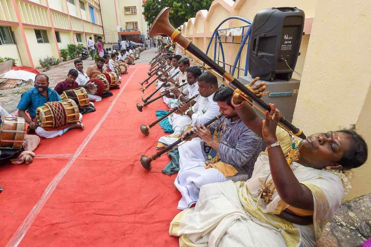 A long line of nadaswaram and mridangam artists in Chennai perform in the open seated opposite each other as they offer prayers to save people from COVID-19