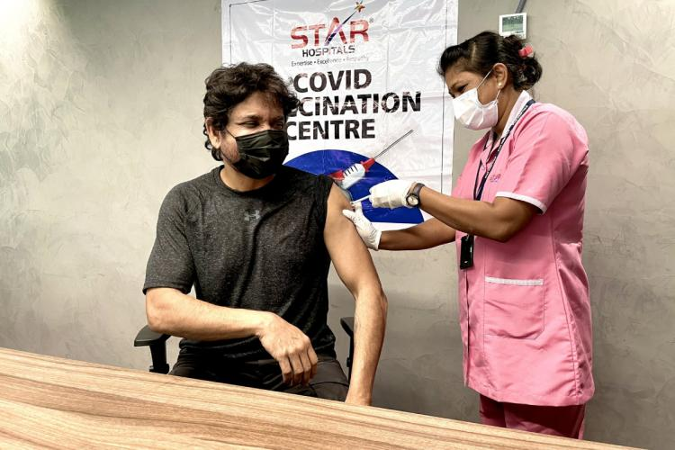 A nurse is seen administering the coronavirus vaccine to actor Nagarjuna