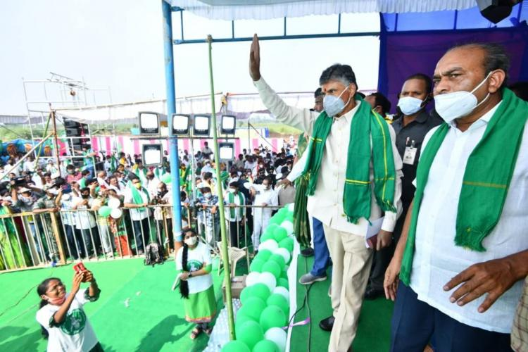 Chandrababu Naidu wearing white clothes and a green scarf standing on a stage waving to protesters in Amaravati
