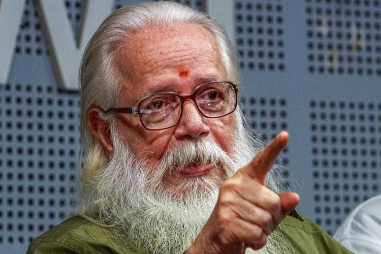 Nambi Narayanan speaking in a press meetHe is seen pointing his finger towards someone in front