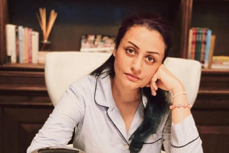 Namrata Shirodkar wearing lavender pyjamas no make up sitting at a table with her face on her hand looking at the camera