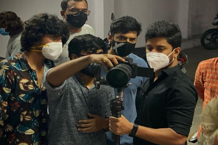 Nani is seen looking at a camera along with other people who are likely to be crew members