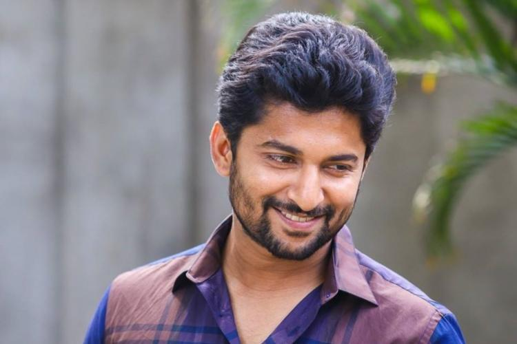 Actor Nani looking down towards his right and smiling wearing a blue and brown shirt