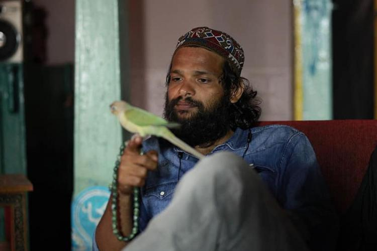 Filmmaker Naranipuzha Shanavas sitting on a couch holding a parrot in hand