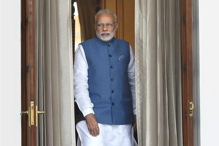 Narendra Modi the Prime Minister of India is standing in his official attire and staring from a room