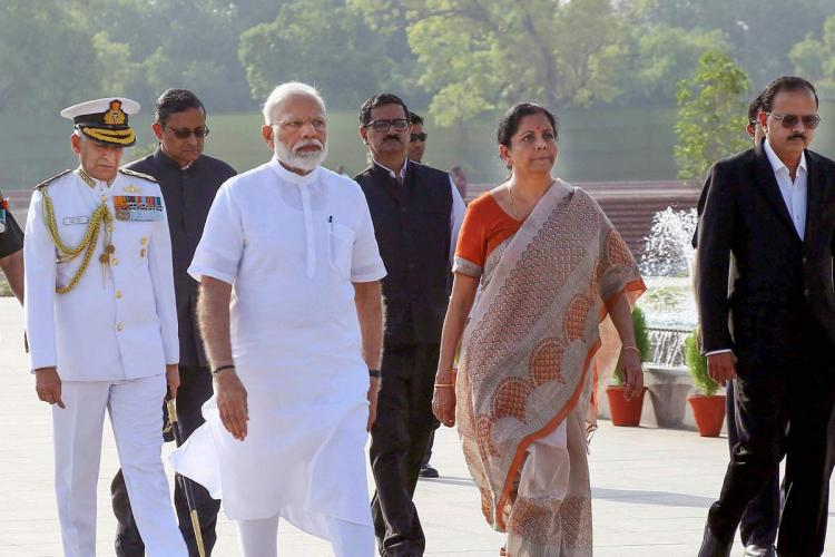 Narendra Modi and Nirmala Sitharaman walk side by side as other officials follow