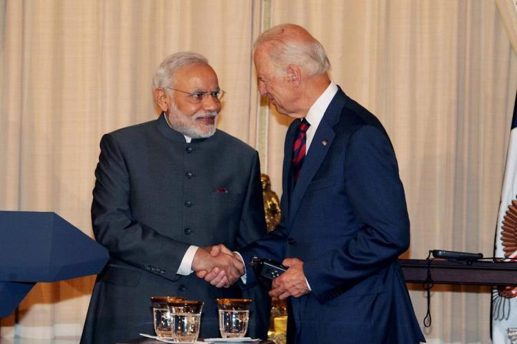 PM Modi shaking hands with Joe Biden dressed in a blue suit