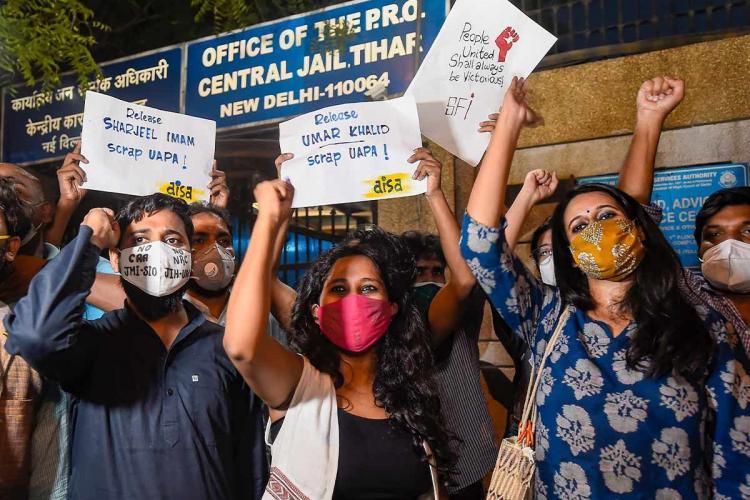 Student activists Natasha Narwal Devangana Kalita and Asif Iqbal Tanha rasing slogans outside Tihar Jail on being released on bail