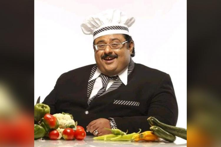 Naushad wearing a white chef's cap and black suit and tie smiles and sits before a number of vegetables