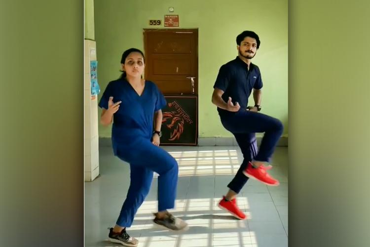 A young man and woman in scrubs dancing