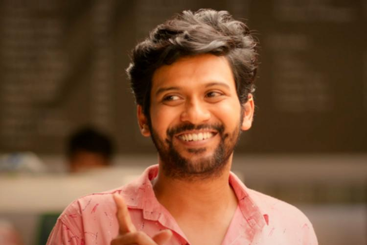 Donning a pink shirt Naveen Polishetty is seen smiling in the screengrab from the movie Jathi Ratnalu
