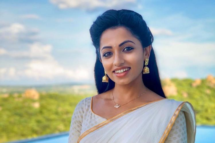 Telugu television actor Navya Swamy in a white saree standing against a clear blue sky in the backdrop