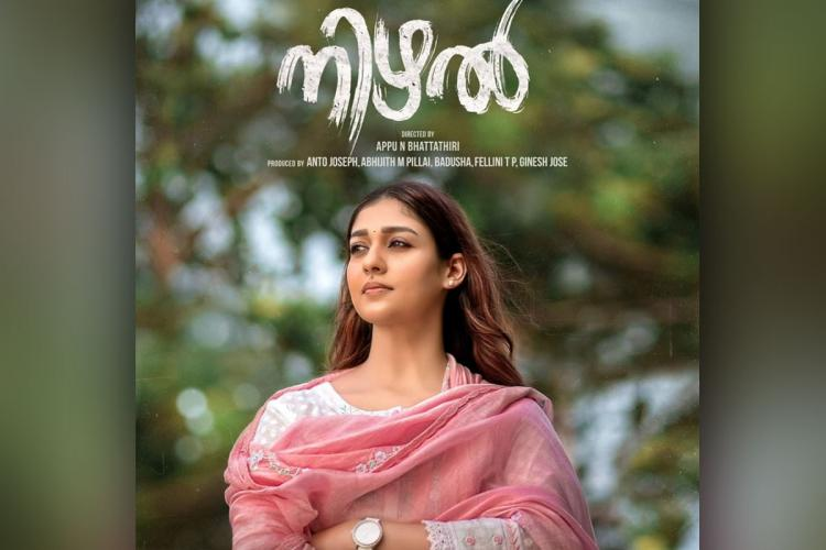 Nayanthara wearing a pink and white kurtha and shawl looks at the distance with a small smile on her face her hair lose and in the background are trees