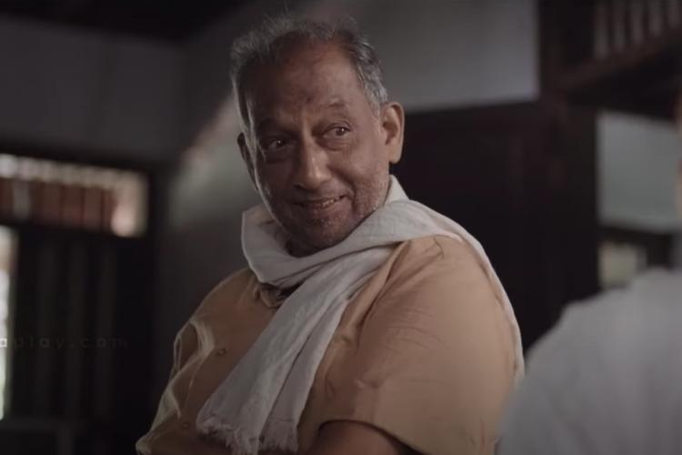Nedumudi sits inside a house looking at someone opposite him, a cream kurtha on him and a white towel wrapped around the shoulders. He looks aged.