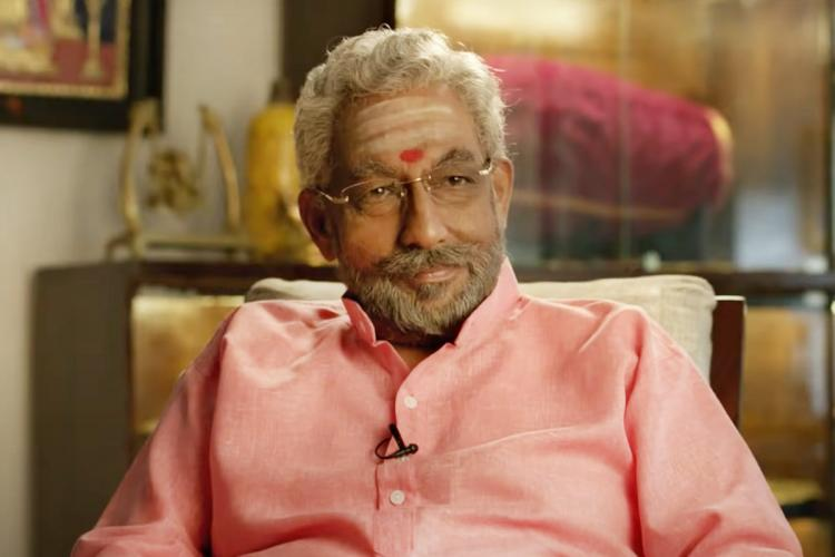 Nedumudi venu in a pink shirt with grey hair and beard and specs sits in a chair and smiles