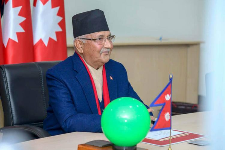 Nepal Prime Minister KP Sharma Oli sitting on a chair at his office He wears a blue blazers and a black cap He is slightly smiling looking towards the front