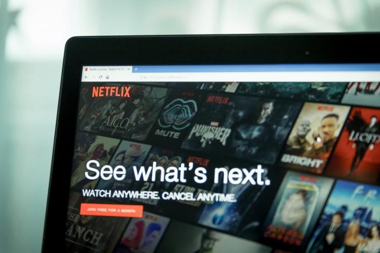Netflix home screen partially visible on a laptop