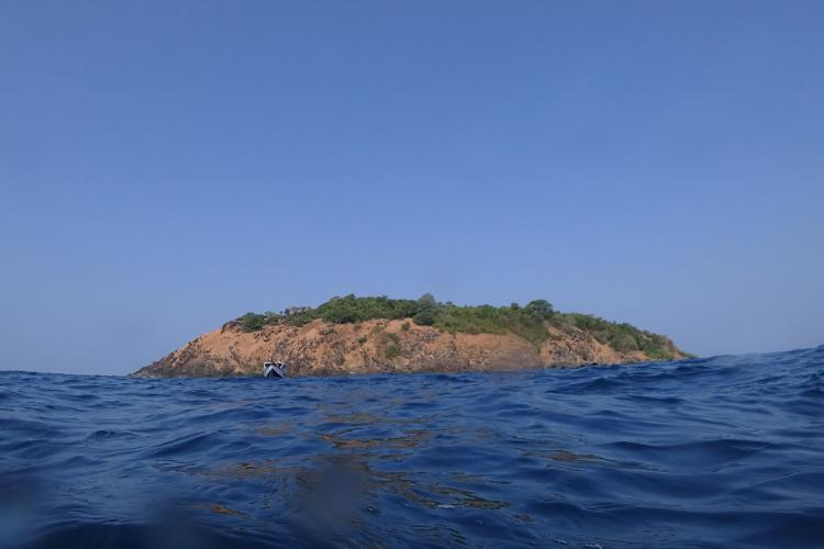 Netrani Island seen from afar The photo is taken probably from a boat approaching the island across a blue expanse of water