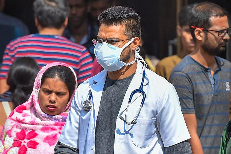 picture of a doctor wearing a mask with some people in the background at a Delhi hospital