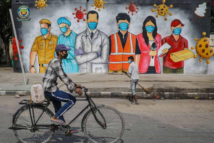 Man on bicycle rides past a mural of frontline workers of the pandemic as another man sweeps the street
