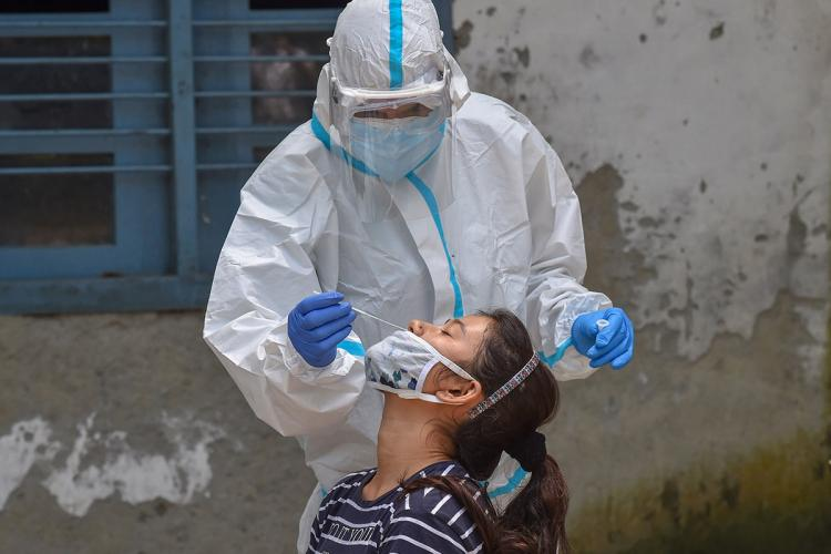 A woman tilts her head back as a nasal swab sample is collected from her by a technician wearing PPE for COVID-19 testing