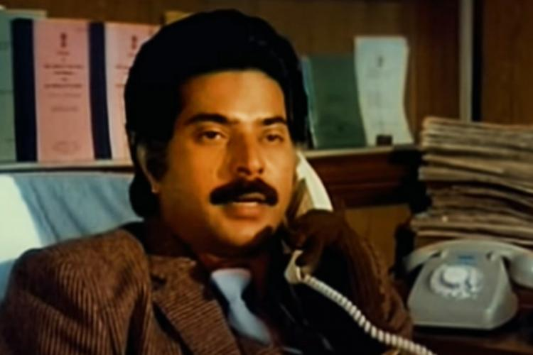 Mammootty in New Delhi movie speaking over the phone wearing a brown shirt with tie