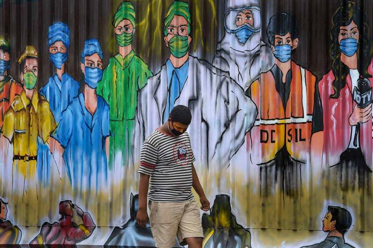 A man walks past a mural in Delhi