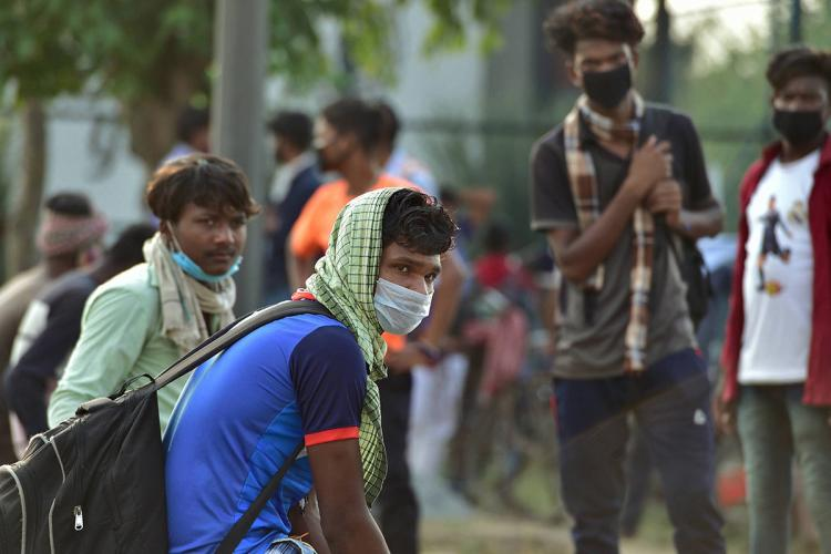 Migrant worker in blue tshirt and backpack sits with his face and head covered