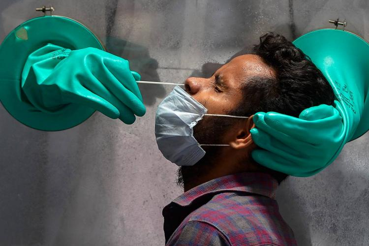 Man in mask getting samples taken by two gloved hands