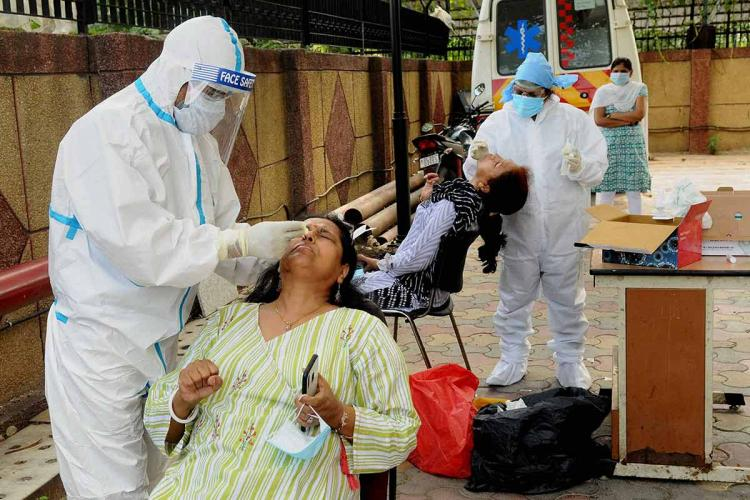 two healthcare professionals take samples from two young women for coronavirus testing on the campus of a new delhi hospital