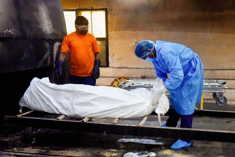 Two men carry out last rites of a coronavirus victim at a crematorium