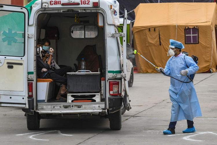 healthworker in ppe sprays disinfectant on an ambulance with people sitting inside in new delhi