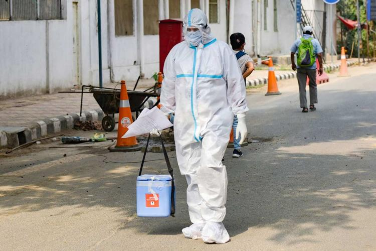 A healthworker in New Delhi walking on the road wearing PPE and holding a bag and some papers