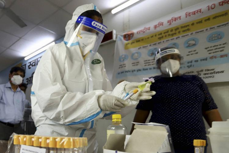 Man in PPE takes samples for COVID-19 and places them
