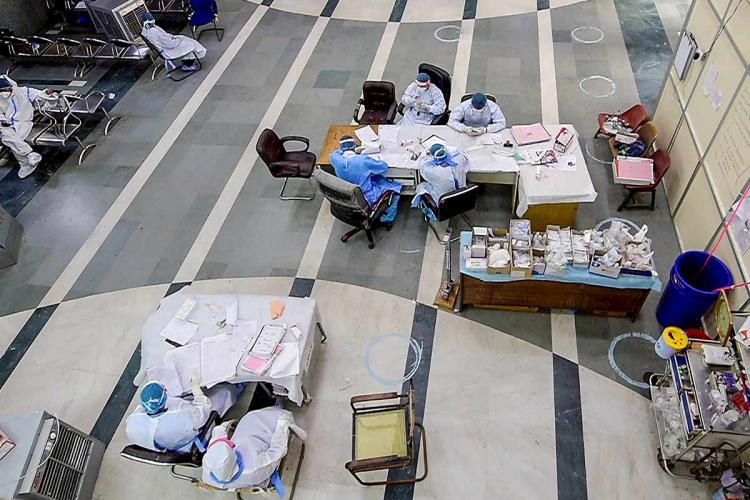 A few health workers sitting at their desks in PPE suits image taken from above