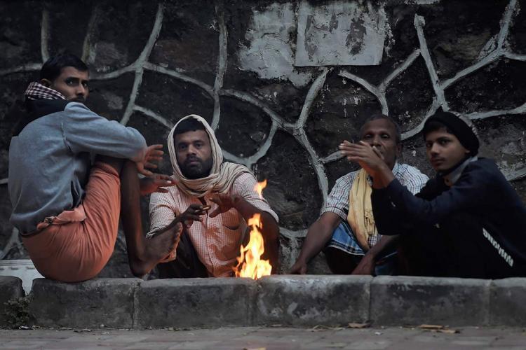 People sit around a bonfire New Delhi
