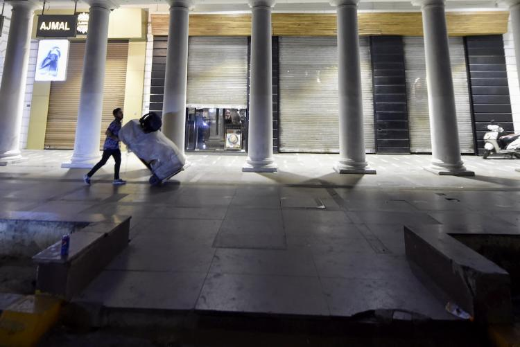 A man pushes a trolley in a deserted space in New Delhi at night owing to the night curfew