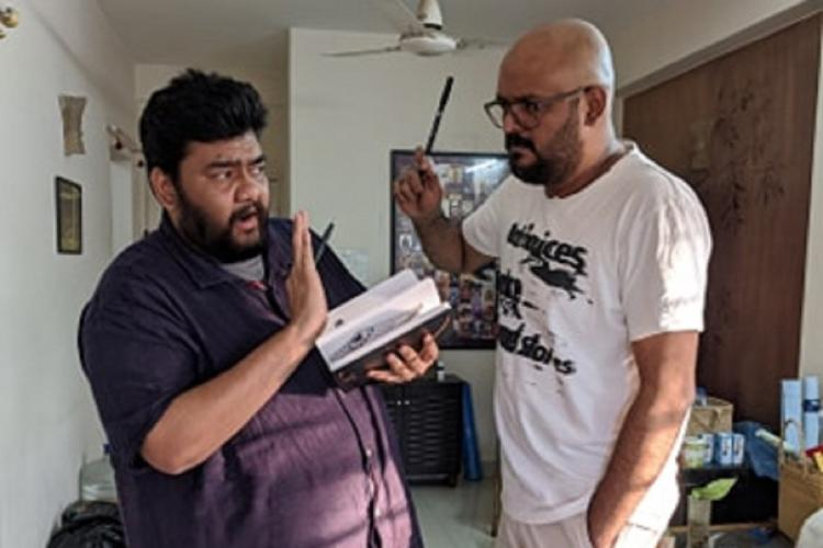 One bearded man wearing violet shirt is mock scolded with a pen by another bearded clean shaven man wearing specs and a white t shirt