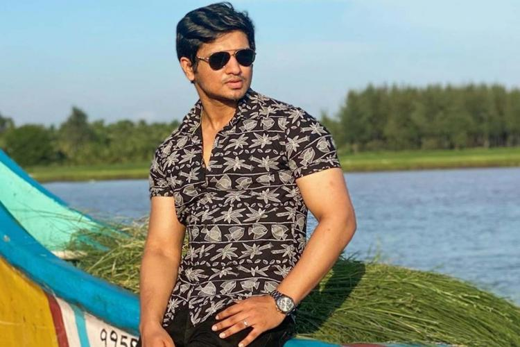 Tollywood actor Nikhil Siddhartha in a black shirt wearing shades looking to his left standing in front of a lake
